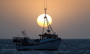 Taste of the sea: the sun rises behind a fishing boat moored off the East beach in Selsey, West Sussex.