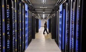 An employee walks past servers at a Facebook data center.
