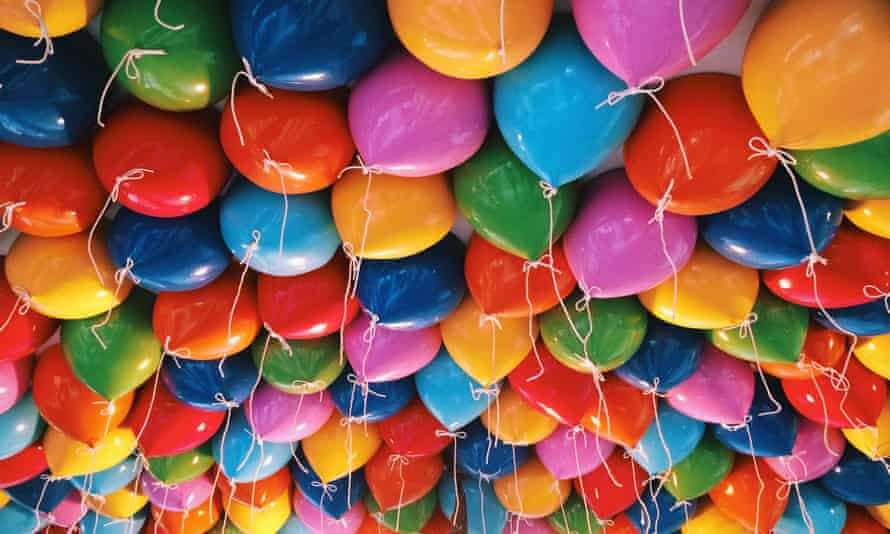 Helium-filled balloons stuck against a ceiling.