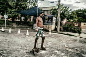 A resident carries food for distribution in City of God at the start of coronavirus epidemic in Rio de Janeiro.