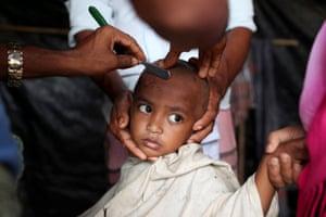 Cox's Bazar, Bangladesh: A Rohingya refugee child gets a haircut in the Palong Khali refugee camp