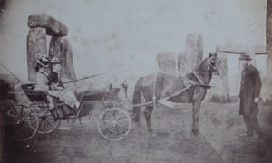 Routh family: two women in cart with horse attached and man standing in fronf of horse, in front of stones