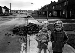 A small boy and girl stand in front of a pile of coal dumped in the street in Peterlee, County Durham, 1966