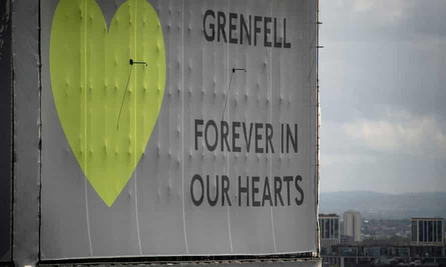 A banner reading 'Grenfell: forever in our hearts' wrapped around the tower block