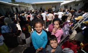 Chidren look at the photographer as Pope Francis delivers a speech at the Moria refugee camp