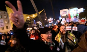 A demonstrator shows a victory sign as he takes part in a march in Warsaw against the rightwing Polish government.