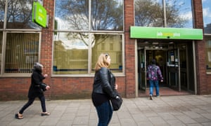 People walk past a jobcentre in London