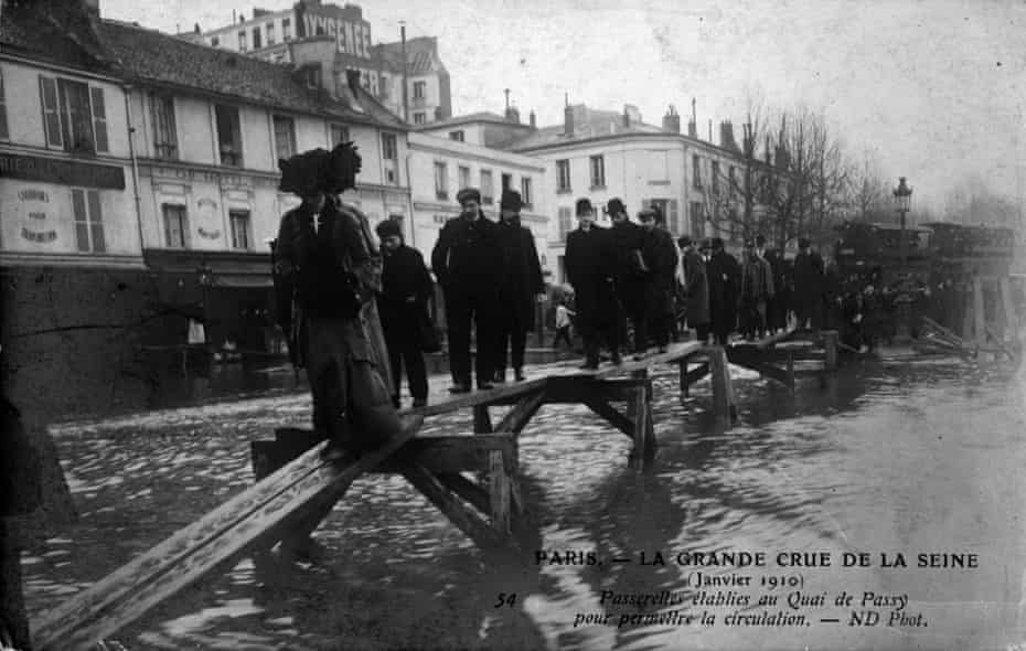 Pedestrians traverse a footbridge erected during flooding of the Seine in January 1910.