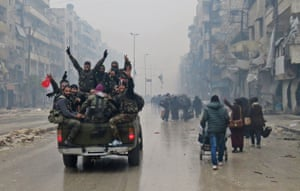Syrian pro-regime fighters gesture as they drive past residents fleeing Bustan al-Qasr