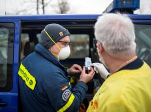 A member of the THW (Technisches Hilfswerk) and member of the ASB (Arbeiter-Samariter-Bund) check the temperature of a box with Pfizer-BioNTech COovid-19 vaccines at a vaccination centre in Bad Windsheim, Germany on December 26, 2020, one day before the country starts its vaccination programme.