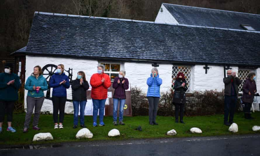 'Human kindness will not be locked down' … people clap as a funeral cortege passes through Glencoe, Scotland.
