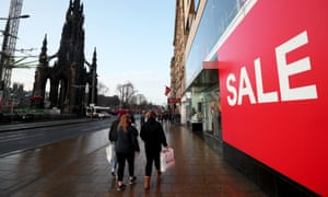 Shoppers pass a sale sign
