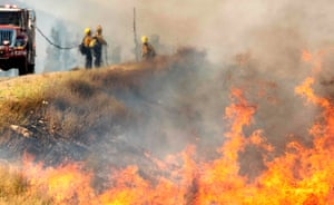 Firefighters are seen through heat as they battle the 'Apple Fire'