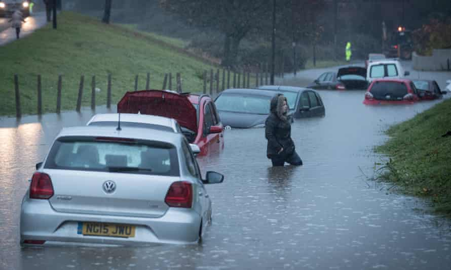 A resident passes cars that have been submerged under several feet of flood water in Hartcliffe.