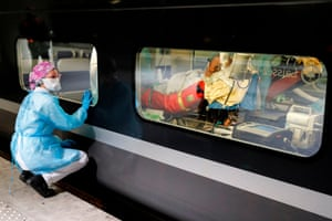A medical worker watches a patient through the window of a medicalised high-speed train at Gare d'Austerlitz railway station in Paris before its departure to evacuate people to Brittany where the outbreak has been confined.