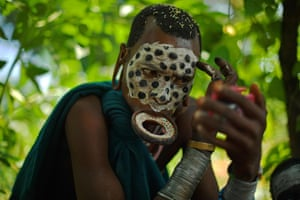 A woman from the Suri tribe wearing a lip plate paints her face