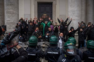 Demonstrators face police officers during a protest against Covid-19 restrictions organised by the 'Io Apro' association of restaurant owners, entrepreneurs and small business owners