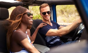 Young Couple Driving Open Top Car