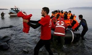 A Red Cross volunteer carries a refugee baby at a beach on the Greek island of Lesbos this month.<br>