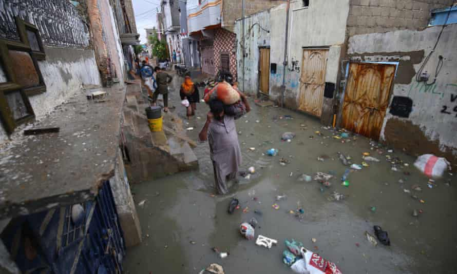 People make their way through a flooded road after monsoon rains in Karachi, Pakistan.