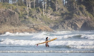 A female surfer wades out into the incoming surf in the waters of the Pacific Rim off of Chesterman Beach, Tofino, Vancouver Island, British Columbia