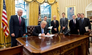 Donald Trump signs the global 'gag rule', surrounded by men.