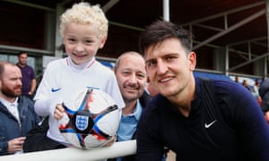 Harry Maguire poses with a young fan at St George's Park on Tuesday.