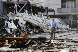 A man looks over destroyed buildings.