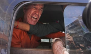 James Ricketson speaks from a prisoner van outside court in Phnom Penh on Friday after he was sentenced to six years' jail