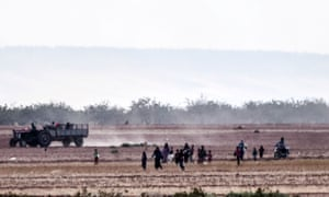 Syrian people run away from clashes between Turkish soldiers and Isis fighters, 12 miles west of the Turkish-Syrian border town of Karkamis, on Saturday.