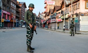 Indian paramilitary troops stand guard during a curfew in Srinagar.