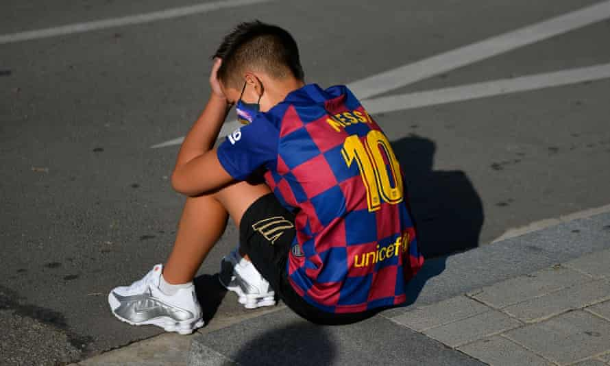 A young Lionel Messi fan appears to be upset as he sits on the pavement outside Barcelona's training ground.