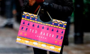 A customer carries a Ted Baker-branded shopping bag