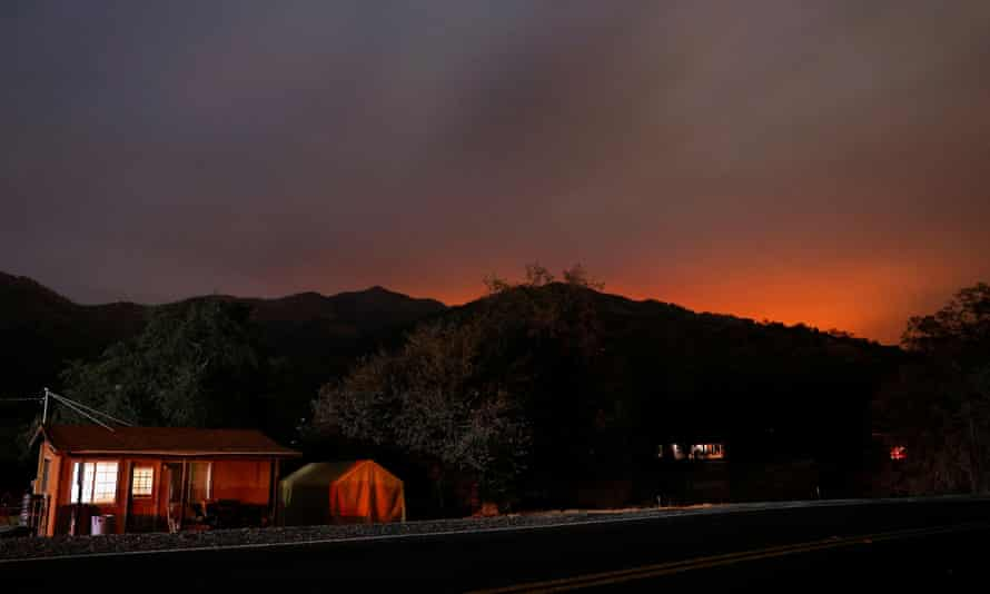 The glow from the KNP Complex fire burning in Sequoia national park is seen in the hills behind homes in Three Rivers, California.