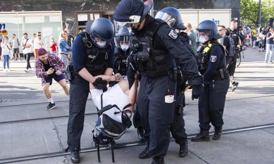 German police detain a protester demonstrating against lockdown measures on Alexanderplatz in Berlin