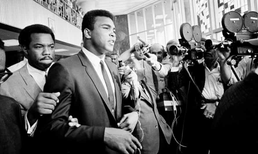Muhammad Ali is confronted by the cameras in 1967 during his Houston trial for refusing induction to the army.