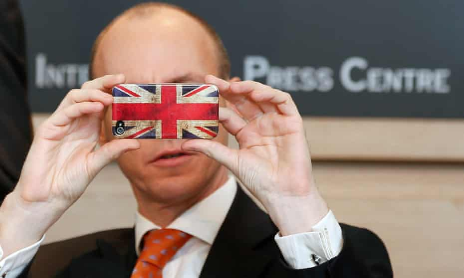 Daniel Hannan takes a picture with his smartphone during a press conference of the Alliance of European Conservatives and Reformists in Brussels