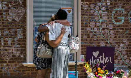 Mourners embrace in front of chalk messages that line the walls outside the buildings where Heather Heyer was killed by a speeding vehicle as she was protesting the Unite The Right rally in Charlottesville, Virginia.