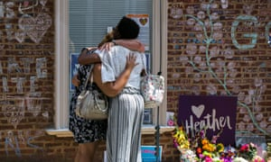 Mourners embrace outside the building where Heather Heyer was killed by a car driven by a white supremacist, in Charlottesville, Virginia.