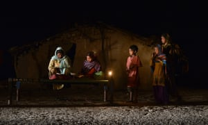 A girl studies by candlelight in an area without electric power in Phillaur, India