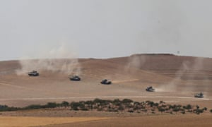 Turkish tanks and members of the Free Syrian Army pass the Syrian border.