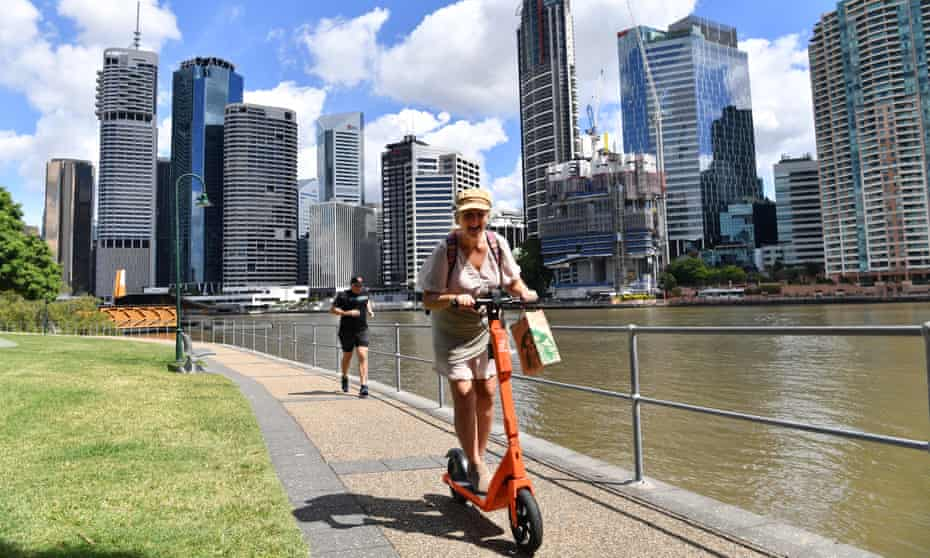 A woman rides an electric scooter beside the Brisbane River