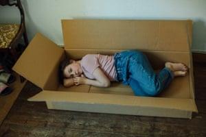 A girl lying in a large cardboard box