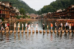 Fenghuang, China: Visitors walk on stone piers across the Tuojiang river in the ancient town of Fenghuang, which nestles on the banks of a winding river and boasts stunning Qing and Ming dynasty architecture