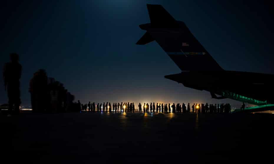 People queue to board a US military aircraft at Kabul airport