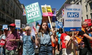 Doctors, nurses, campaigners, medical staff and NHS supporters protest against funding cuts at a rally in London.