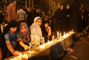 Baghdad, Iraq People light candles at the scene of a massive car bomb attack in Karada, a busy shopping district where people were shopping for the upcoming Eid al-Fitr holiday