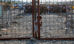A young boy slips through a narrow opening in a gate inside a refugee camp in Macedonia.