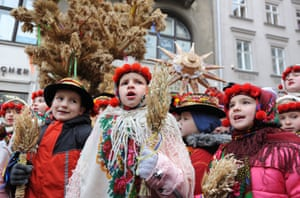 Lviv, Ukraine: people sing Christmas carols as they carry decorated stars of Bethlehem and sheaves of wheat during a parade