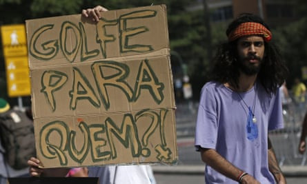A protestor next a sign to reading 'Golf for whom?' during a protest on Copacabana beach against the Olympics